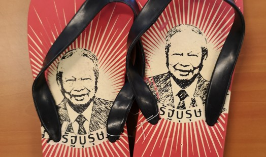 A pair of flip-flops with the portrait of Prem Tinsunalond